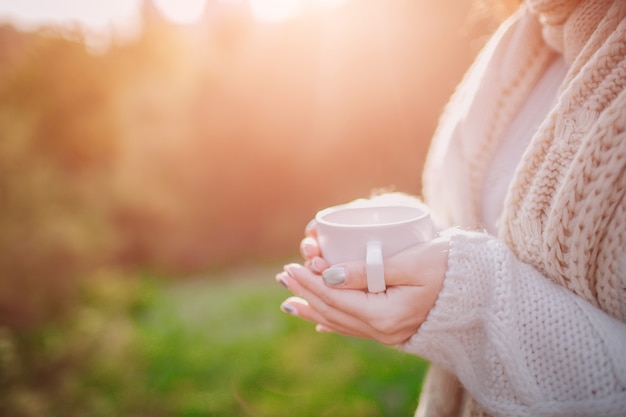 Una giovane ragazza con in mano una tazza di bevanda calda e sorridente in un bosco in autunno