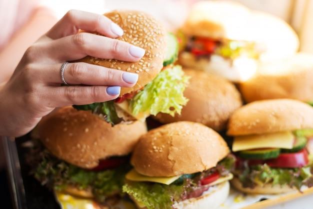 Tenuta della ragazza in hamburger femminile delle mani degli alimenti a rapida preparazione, pasto americano non sano di calorie su fondo