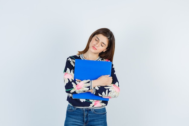 Cartella della holding della ragazza, chiudendo gli occhi in camicetta floreale, jeans e guardando stanco, vista frontale.