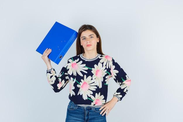 Ragazza con cartella vicino alla testa in camicetta floreale, jeans e guardando perplesso, vista frontale.