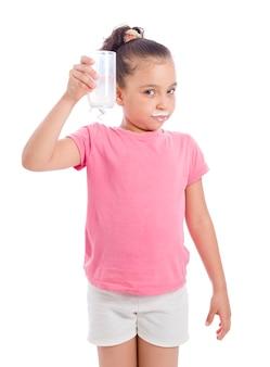 Giovane ragazza con un bicchiere di latte su sfondo bianco