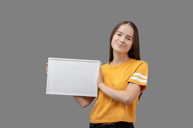 Giovane ragazza che tiene una cornice bianca orizzontale con un modello in mano, sorridente, isolata su sfondo grigio