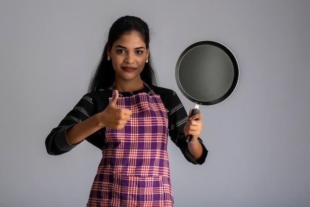 Ragazza giovane azienda utensili da cucina spatola e padella su un muro grigio