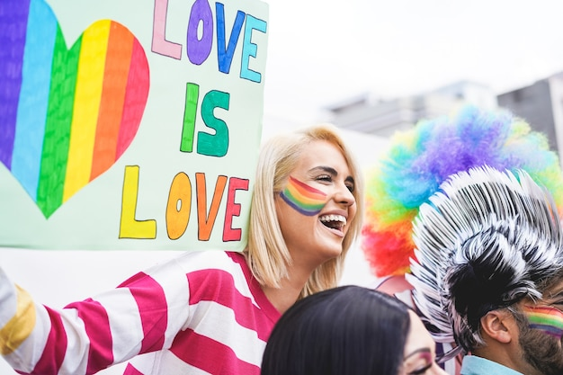 Ragazza che tiene un banner love is love a una parata del gay pride