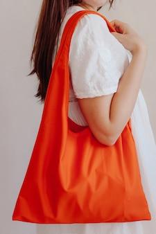 Ragazza che tiene una borsa della spesa di cotone arancione sulla spalla