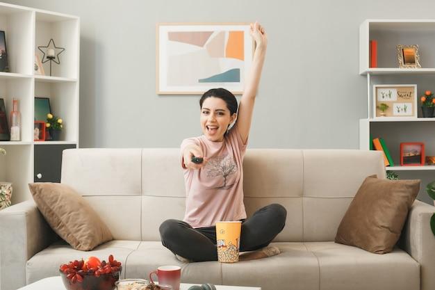 Ragazza giovane tenendo fuori il telecomando della tv alla telecamera seduta sul divano dietro il tavolino da caffè in soggiorno