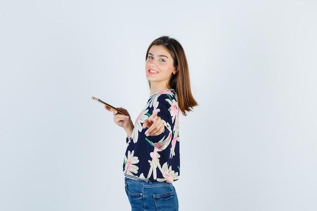 Giovane ragazza che tiene il telefono, puntando alla telecamera, in piedi di lato in camicetta floreale, jeans e sembra allegra.