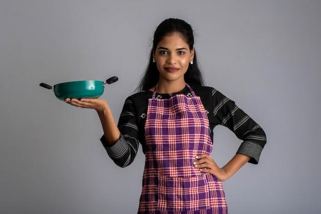 Ragazza giovane azienda e posa con utensili da cucina pan su un muro grigio