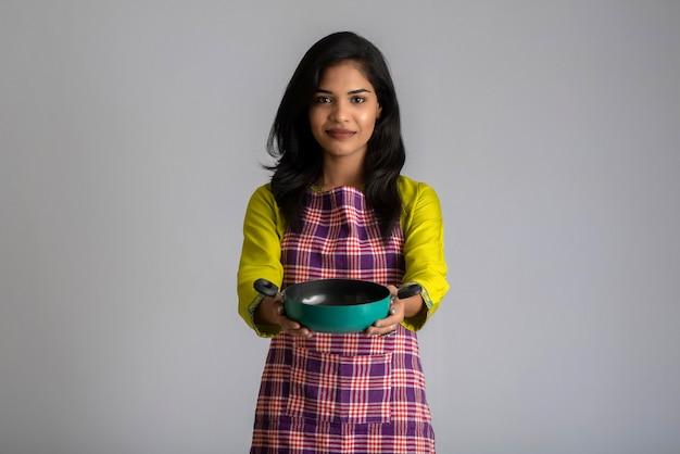 Ragazza giovane azienda e in posa con utensili da cucina padella su un grigio