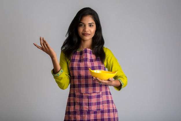 Ragazza che tiene e che posa con il piatto e la ciotola degli utensili da cucina su un gray