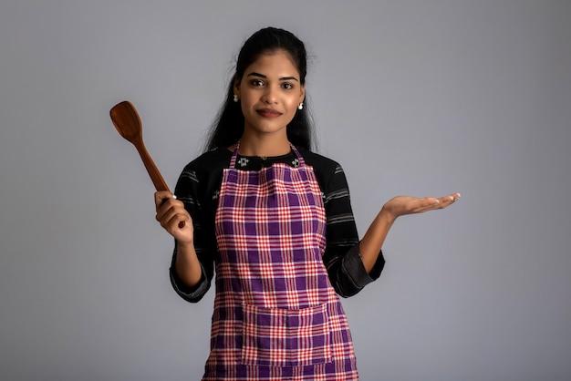 Ragazza giovane azienda e in posa con utensili da cucina spatola su un muro grigio