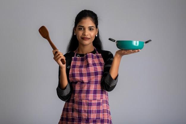 Ragazza giovane azienda e in posa con utensili da cucina spatola e padella su un muro grigio