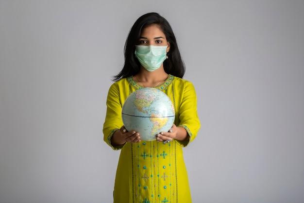 Ragazza giovane azienda e posa globo del mondo con una maschera medica su sfondo grigio.