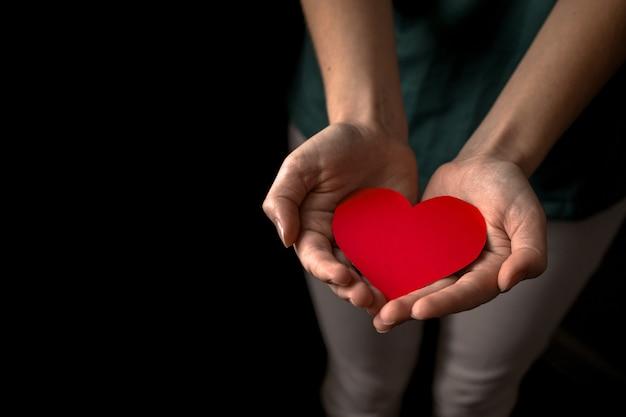 Ragazza giovane azienda cuore rosso su sfondo nero. assicurazione sanitaria, giornata del donatore di organi, concetto di beneficenza. concetto di giorni di salute mondiale, mentale e del cuore. tutte le vite contano foto