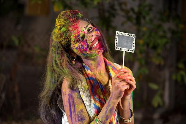 Ragazza che tiene la piccola tavola in occasione della festa di holi con facce dipinte con colori in polvere, con un tocco di colore.