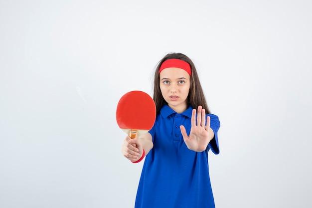Una giovane ragazza con racchetta da ping pong e mostrando il segnale di stop