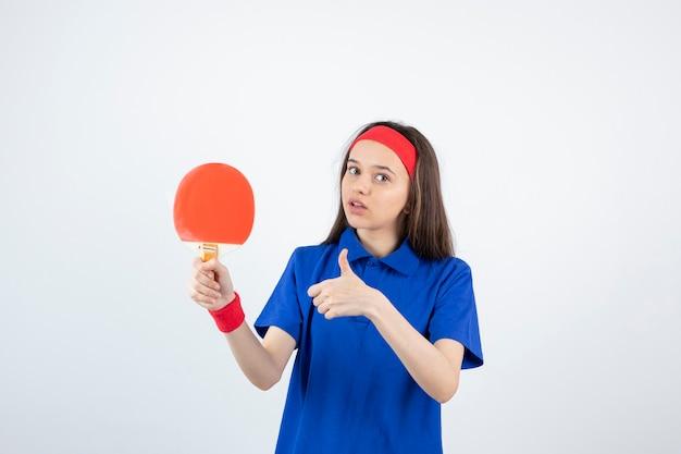 Una giovane ragazza con racchetta da ping pong e mostrando il pollice in su