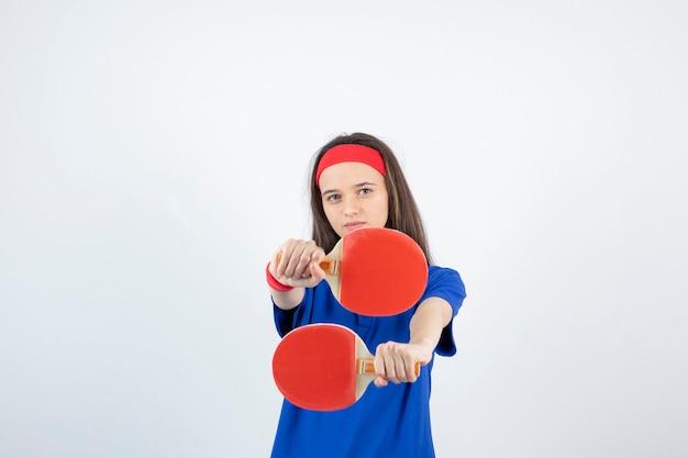 Una giovane ragazza con racchette da ping pong su un muro bianco