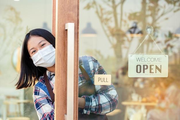 Una giovane ragazza in possesso di tablet con dire ciao e avere un cartello aziendale che dice benvenuto siamo aperti nella caffetteria o nella porta del ristorante