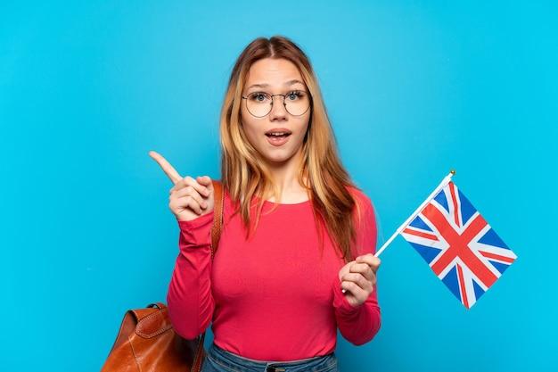 La ragazza che tiene una bandiera del regno unito sopra la parete blu isolata che intende realizzare la soluzione mentre solleva un dito