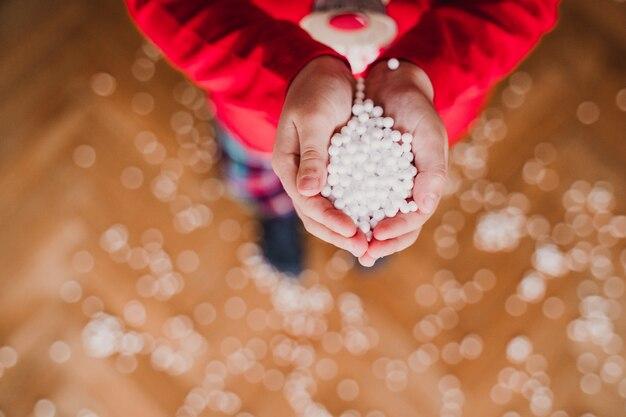 La tenuta della ragazza con la neve artificiale delle mani si sfalda a casa