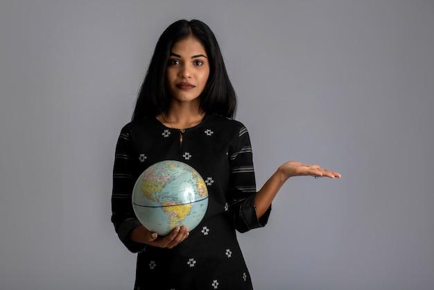 Ragazza che tiene il globo del mondo e posa sul grigio.