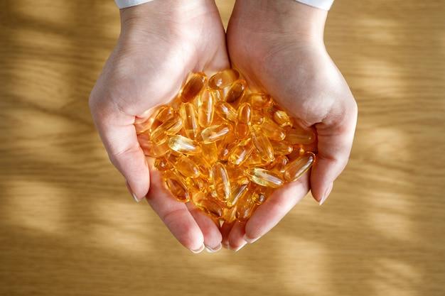 Una giovane ragazza tiene tra i palmi molte capsule di olio di pesce.