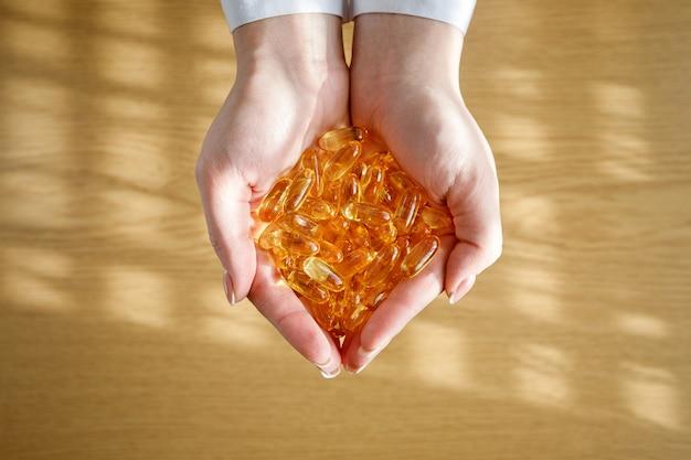 Una giovane ragazza tiene tra le mani molte capsule di olio di pesce.