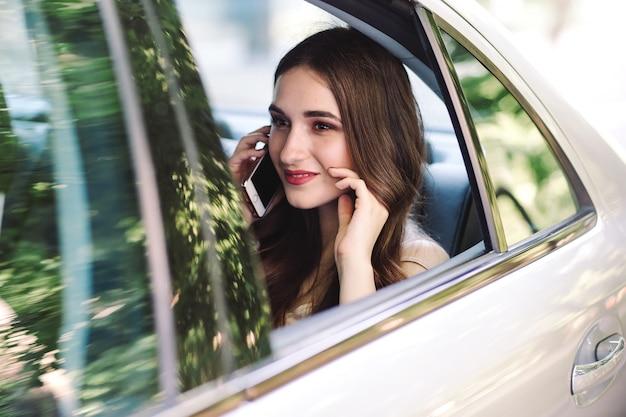 Una ragazza è seduta sul sedile posteriore di un'auto e parla al telefono.
