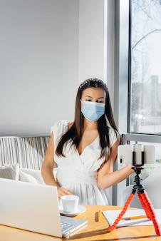 Una giovane ragazza è seduta in un caffè con una maschera e dirige un video blog. comunicazione alla telecamera.