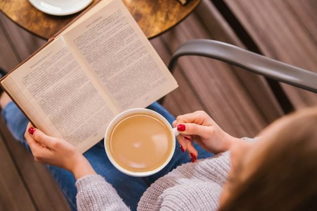 Una giovane ragazza è seduta in un caffè e sta leggendo un libro. la ragazza beve caffè o cacao. atmosfera accogliente e piacevole tempo libero. riposo e relax.