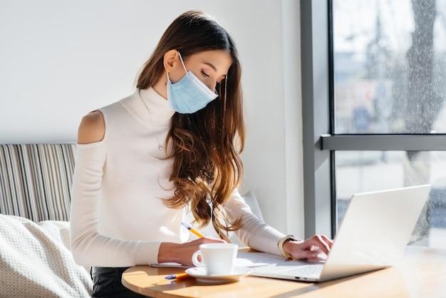 Una giovane ragazza è seduta in un bar con indosso una maschera e lavora al computer.