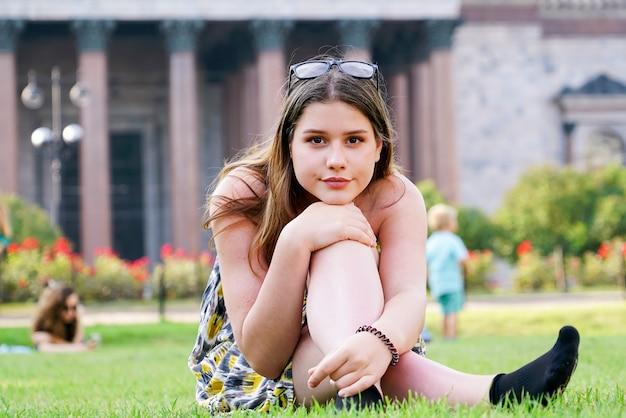 Giovane ragazza è seduta sull'erba verde contro di un antico tempio. san pietroburgo.