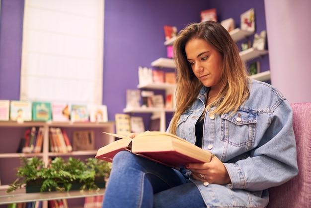 Una giovane ragazza è seduta a leggere un libro con uno sfondo viola
