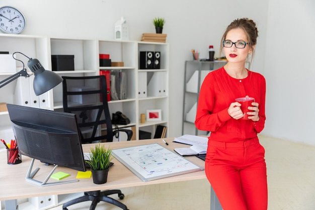 Una ragazza è in piedi appoggiata su un tavolo e con in mano una tazza rossa.
