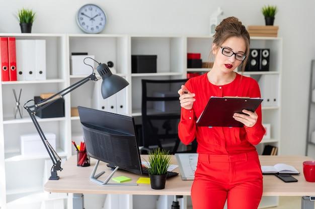 Una ragazza è in piedi appoggiata a un tavolo e tiene in mano una matita e documenti.