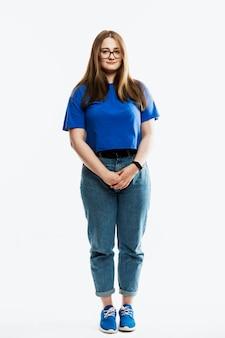 Una ragazza in jeans e una maglietta blu è in piedi. a tutta altezza. isolato su uno sfondo bianco. verticale. Foto Premium