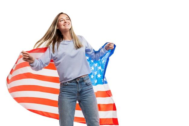 Una ragazza in jeans e una canotta blu tiene una bandiera americana e ride. celebrando la festa dell'indipendenza e il patriottismo. . spazio per il testo.