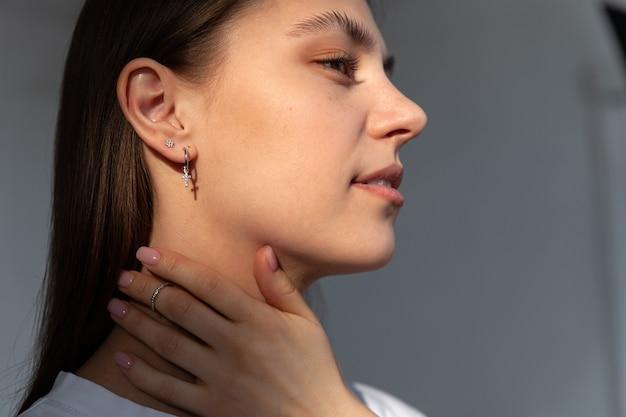 Modello di gioielli da ragazza in moderni orecchini rotondi in argento a forma di croce, mano con anello, negozio di accessori di gioielleria moderna di concetto, luci del sole