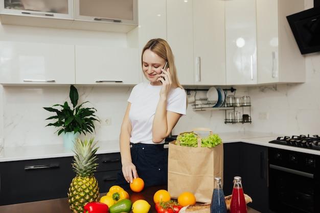 Giovane ragazza in cucina tenendo il telefono e guardando frutta e verdura sul tavolo.