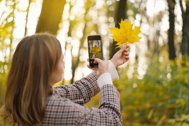 La ragazza ride e fotografa le foglie di autunno al telefono il concetto di mobilità di stile di vita