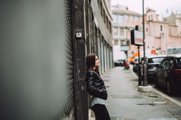 Giovane ragazza appoggiata al muro della città