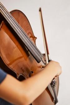 Ragazza che impara a suonare il violoncello a casa
