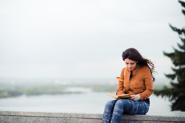 Ragazza in cappotto di cuoio che si siede con il libro contro il riverview un giorno di molla di autunno freddo