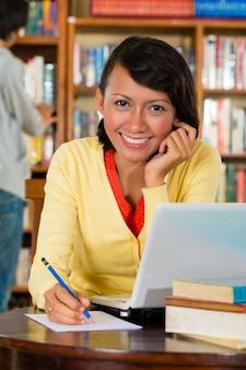 Ragazza in biblioteca con il computer portatile