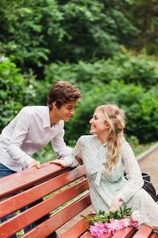 Una ragazza in un vestito leggero in estate si erge e tiene in mano fiori, peonie, un bouquet, un regalo, un appuntamento, in attesa, una panchina, gli amanti,