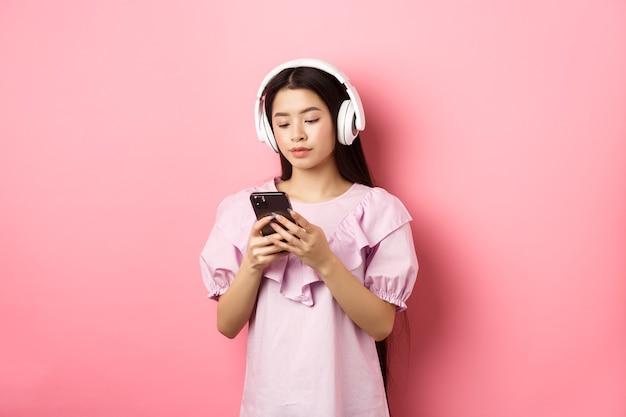 Ragazza giovane ascoltando musica in cuffia e chiacchierando sul telefono cellulare, in piedi in abito su sfondo rosa.