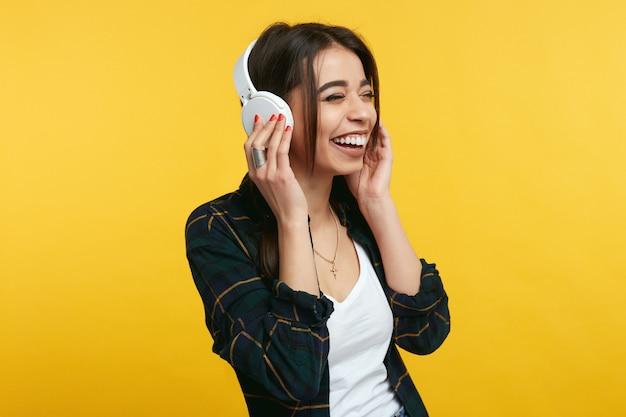 Musica d'ascolto della ragazza e sorridente sopra lo studio giallo