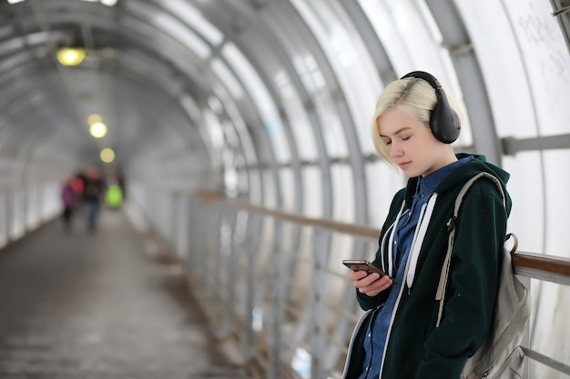 La ragazza ascolta musica in grandi cuffie nel tunnel della metropolitana