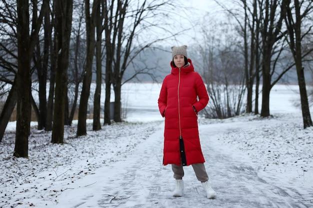 Una giovane ragazza con un lungo cappotto rosso imbottito si trova nella foresta invernale.